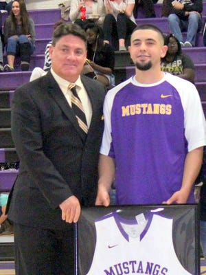 Head coach Jeff Law, left, poses with senior Adam Kesler during the final game of the Mustangs this season.