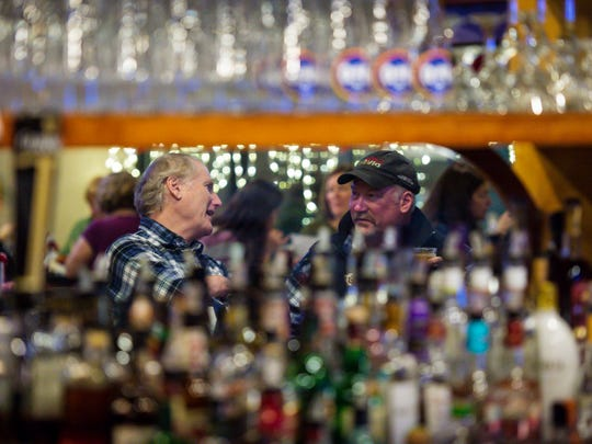 A pair of patrons enjoy a pint and a smile at the Church Street Tavern in Burlington on Tuesday, December 6, 2016.