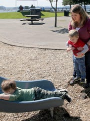 Tammy Harder holds her Marcus, as enjoys the playground with his brother Lucas, 4, on an outing to Silverdale Waterfront Park.