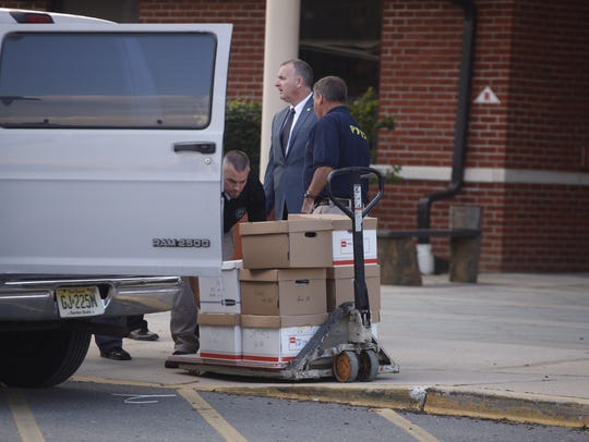 Police used a fork lift to remove dozens of boxes from