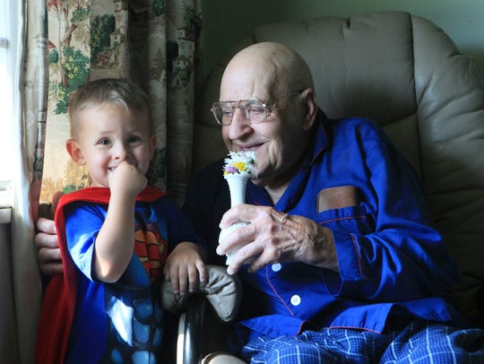 Luke Torres and his great grandfather Ed Shapley enjoy flowers.