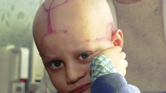 In this file photo taken on Wednesday, March 19, 1996, five-year-old Alek Zhloba, who suffers from leukaemia, is held by his doctor in the children's cancer ward of the Gomel Regional Hospital, in Gomel, Belarus.