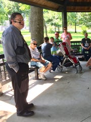 Local historian Frank Nally talks to history walk attendees during a stop at the gazebo in Central Park