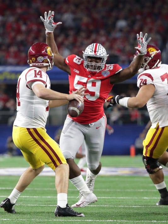Ohio State defensive lineman Tyquan Lewis (59) closes in on Southern California quarterback Sam Darnold (14) during the first half of the Cotton Bowl NCAA college football game in Arlington, Texas, Friday, Dec. 29, 2017. (AP Photo/LM Otero)
