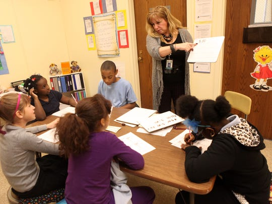 MeChele Markajani, a consultant teacher at School 12, works with a group of students, Jasmine Gunther, Trevyon Rowe, Arianna King, Jahnessa Elliott and Anselie Gaffney on addition and subtraction with money.