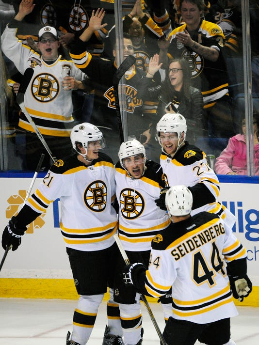 Boston Bruins Loui Eriksson (21) celebrates a third-period goal by Brad Marchand, center, along with teammates Dougie Hamilton (27) and Dennis Seidenberg (44) in front of Boston fans during an NHL hockey game against the Buffalo Sabres, Thursday, Oct., 30, 2014, in  Buffalo , N.Y. Boston won 3-2 in overtime. (AP Photo/Gary Wiepert)