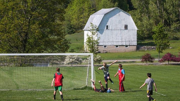 The Leelanau County Poor Farm barn is seen in the background