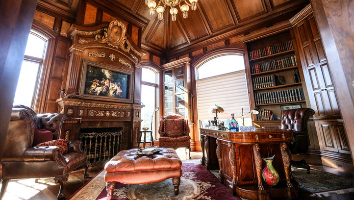 Mahogany paneling wraps the dramatic library, up and