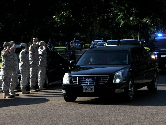 Airmen from Dyess Air Force Base salute as the funeral