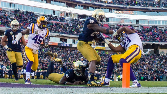 Notre Dame Fighting Irish running back Tarean Folston (25) scores a touchdown as Louisiana State Tigers safety Jamal Adams (33) defends in the second quarter at LP Field.