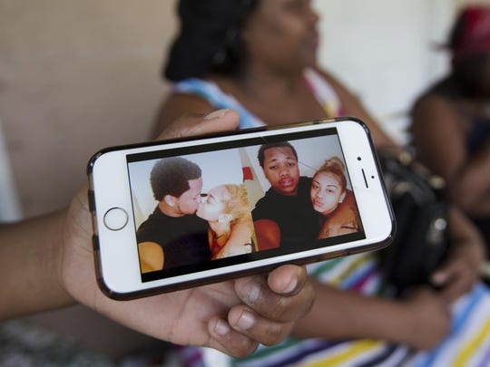 The sister of Michael Kelly, 19, displays a photo of him and his girlfriend, Starlette Pitts, 17, at her east Fort Myers home on Wednesday. Sherri Flemming, in background, confirmed that her son, Michael was killed in a home on 21st Street SW in Lehigh Acres. The Lee County Sheriff's Office said Starlette Pitts was also killed along with her mother, Dorla Pitts.