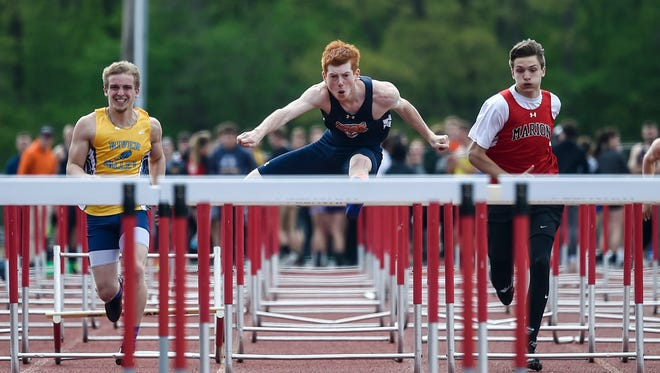 Gallon's Colin McCullough with River Valley's David Blanton on the left and Harding's Hunter Peterson on the left bounds over the hurdles during the boys 110-meter race during the MOAC Championships this year at Pleasant.