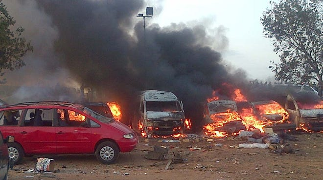 Vehicles burn after a bombing on April 14 in Abuja, Nigeria. The attack appeared to be orchestrated by Boko Haram.