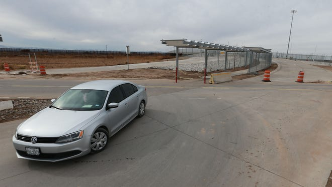 A car turns on a road which leads to the U.S. inspection area at the Tornillo port-of-entry Friday. The new bridge which will connect the U.S. and Mexico is in the background right. It is fenced off awaiting the completion of construction on the Mexican side of the span.