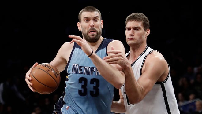 Memphis Grizzlies' Marc Gasol (33), of Spain, drives past Brooklyn Nets' Brook Lopez (11) during the first half of  Monday in New York.