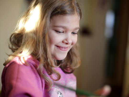 Rya Radford, 7, works on an art project before dinner