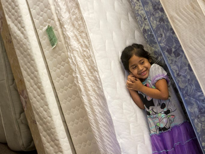 Yesica Jose, 5, hides between mattresses at the St. Matthews House Thrift Store in Bonita Springs as her parents shop for furniture on Saturday, July 12, 2014. Her family had to leave the Manna Christian RV Park when it closed, and they have now moved into an apartment. An anonymous donor saw their story and bought the family some of the things they needed to furnish their home.