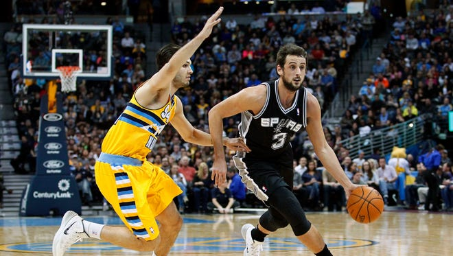 San Antonio Spurs shooting guard Marco Belinelli (3) dribbles the ball as Denver Nuggets shooting guard Evan Fournier (94) defends.