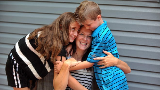 Tiffanie Miller gets a hug from her daughter Brianna, 11, and son Nathan, 7, at their home in Millville, Wednesday, Aug. 3, 2016.