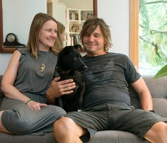 Monica Hall Olszewski and Paul Olszewski pose in the living room of their West Asheville home with their dog, Marti Lukin. The couple have remodeled the original 960-square-foot vinyl ranch home into what it is today.