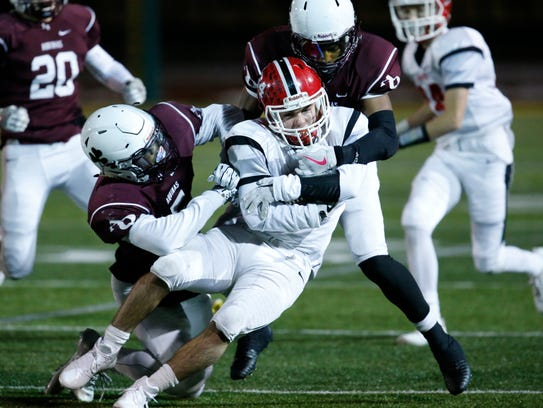 Aquinas' T.J. Jones and Marlek Connor Jr. tackle Lancaster's Andrew Hersey during the Class AA state regional at SUNY Brockport. Both players named all-state.