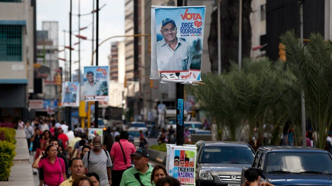 Pedestrians walk along a street adorned with campaign banners promoting Jorge Rodriguez, the Libertador Municipality mayoral ruling party candidate, in Caracas, Venezuela, on Dec. 4, 2013.