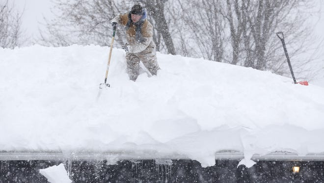 Amid an epic lake-effect snow storm in November 2014, Tom Mudd clears snow from the roof of his house in the Buffalo suburb of Cheektowaga.