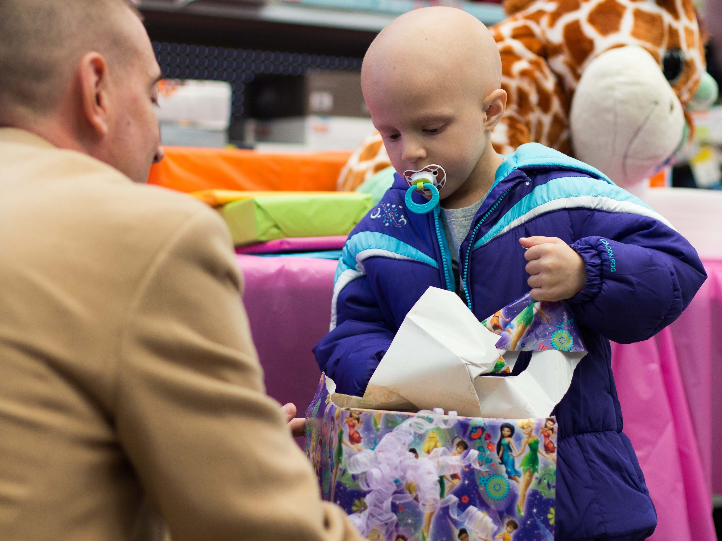 In this 2014 photo, Nattaly Brown, then 4, opens gifts