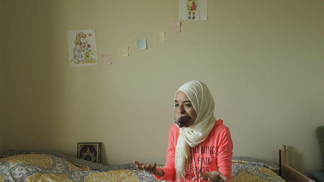 University of Akron graduate student Lamise ElBetar sits in her dormitory room where the picture on the wall next to her bed reminds her of herself and her twin sister.