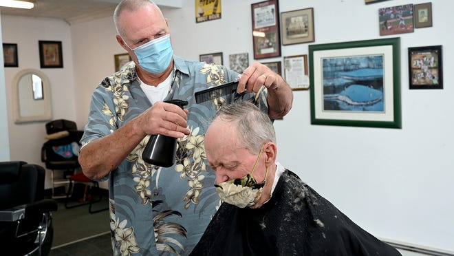 Retiring Milford barber Tom Stock cuts customer Jerry Tardif's hair Friday in Stock's Main Street shop. Stock is retiring Aug. 29 after 50 years cutting hair, first in Hopedale and later in Milford.