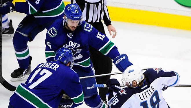 Dec 22, 2013; Vancouver, British Columbia, CAN; Winnipeg Jets forward Bryan Little (18) and Vancouver Canucks forward Brad Richardson (15) fight during the second period at Rogers Arena. Mandatory Credit: Anne-Marie Sorvin-USA TODAY Sports   ORG XMIT: USATSI-137746 ORIG FILE ID:  20131222_lbm_as9_242.JPG