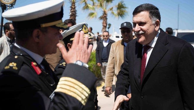 Fayez Serraj, from the U.N.-brokered Libyan unity government, is greeted as he arrives in Tripoli on March 30, 2016.