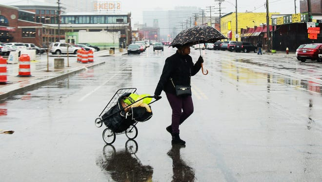 People shop at Eastern Market in Detroit despite the wet and icy weather on Saturday, Jan, 3, 2015.