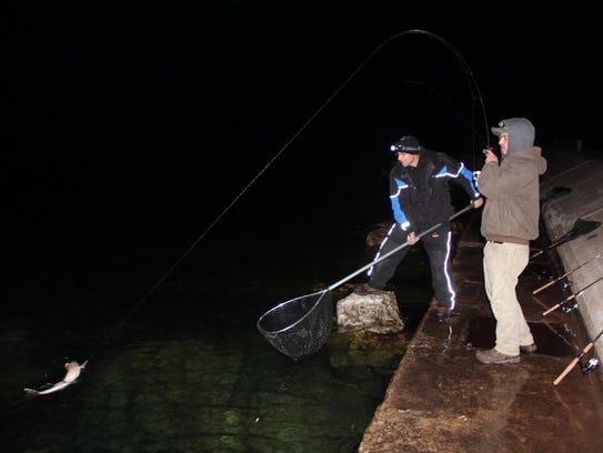Joe Murphy (right) of Waukesha reels in a 31-inch walleye