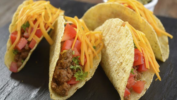 Tacos with ground beef, cheese, vegetables, and guacamole
