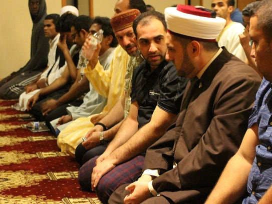 Imam Didmar Faja (second from right) speaks to United