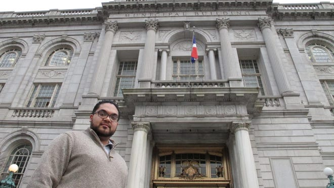 Juan Hernandez, an aide to a City Council member, poses outside City Hall in Hartford, Conn. Hernandez, 25, is among millennials nationwide with student debt who are worried about being able to qualify for a loan and come up with a down payment for a home.