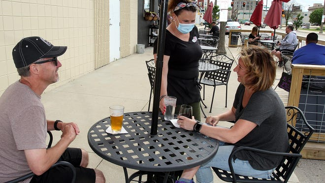 Renee Barr, center, serves drinks to Angie Damin, right, and Chad Damin at Pub 219 on Friday, May 29, 2020, in downtown Freeport.