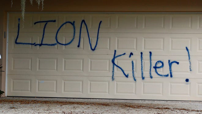 "Vandals spray-painted ""lion killer!"" on the garage door of Walter Palmer's vacation home in Florida."