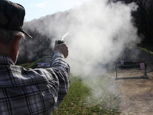 A cloud of black powder smoke erupts from Bob Johnson's 1860 Colt .44-caliber revolver as he target shoots at the
