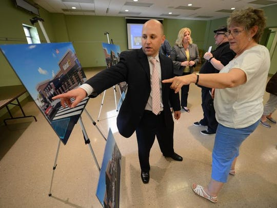 Daniel Contadore of MMA Architects, left, explains the details of the revamped Broadway Walmart store plan to downtown resident Mary Veldkamp at an informational open house at the Neville Public Museum.