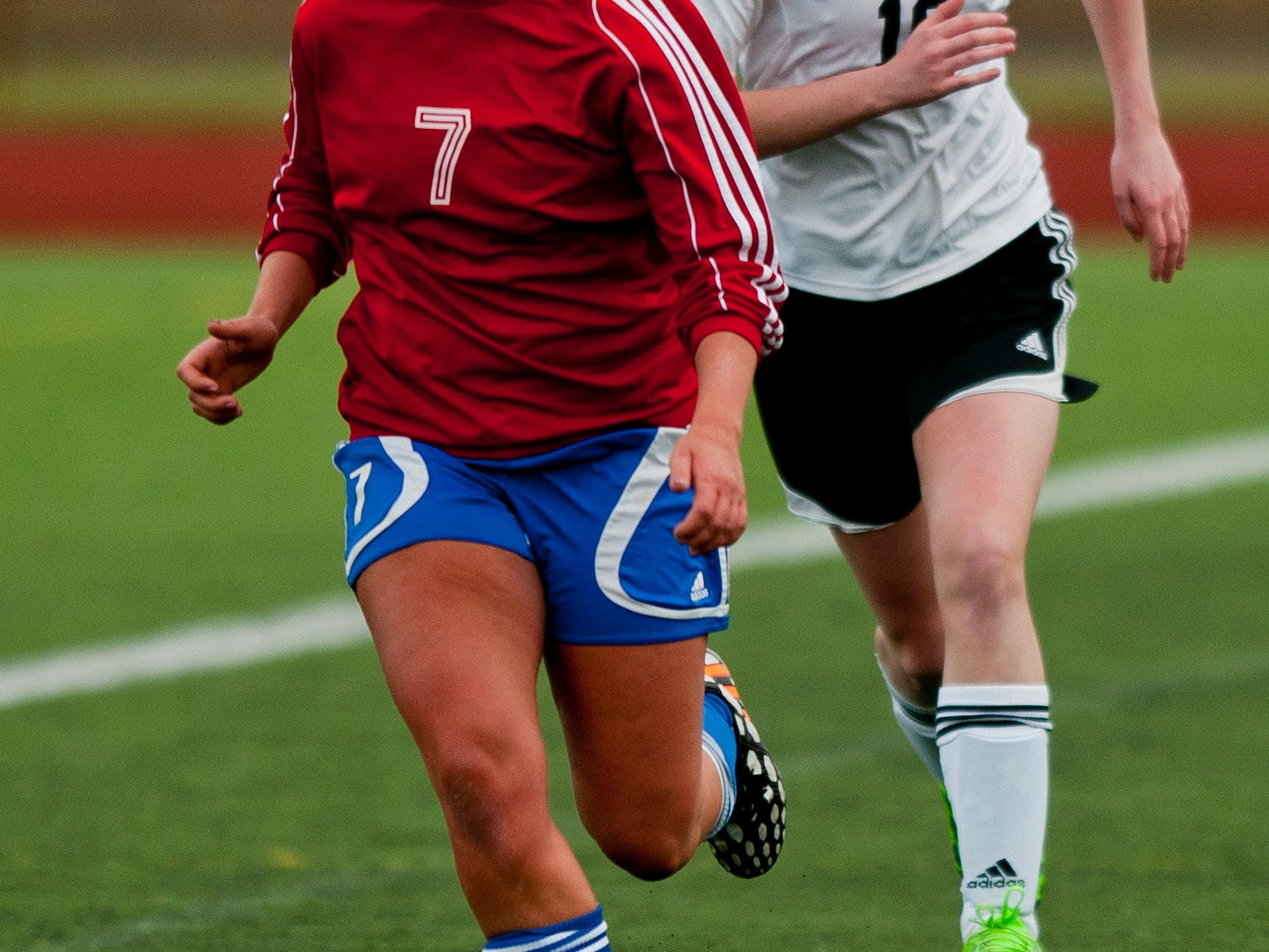 St. Clair's Laura Bluhm drives the ball down field in front of Marine City's Sydnee Frank during a soccer game Wednesday at East China Stadium.