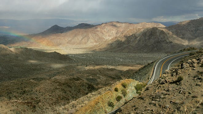 In this file photo, cloudy weather rolls into the Coachella Valley causing a small half rainbow, at left, above the hills near Highway 74 just above Palm Desert.