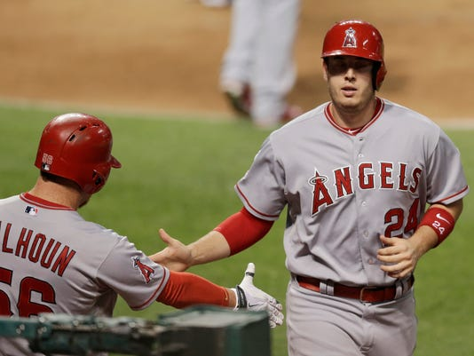 Los Angeles Angels designated hitter C.J. Cron, right, is congratulated by Kole Calhoun after Cron scored on a single by Kaleb Cowart during the fifth inning in a baseball game against the Cleveland Indians, Friday, Aug. 28, 2015, in Cleveland. (AP Photo/Tony Dejak)