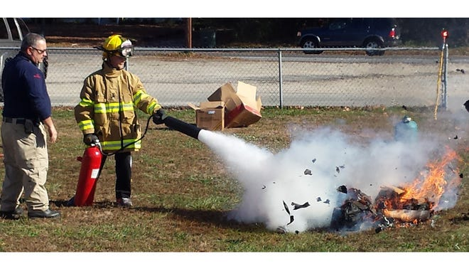 Alex Baldosaro, a sixth grader at Caroline L. Reutter School, demonstrates how to extinguish a fire, as his father, Fire Chief Anthony Baldosaro, looks on, during a fire safety presentation for fifth graders at the school.