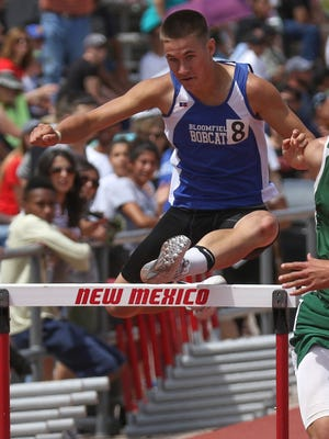 Bloomfield's Drew Smith jumps over the final hurdle in the 300-meter hurdles on Saturday at the University of New Mexico Track and Field Complex in Albuquerque.