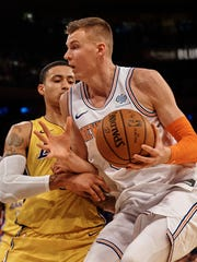 New York Knicks' Kristaps Porzingis, right, drives to the basket against Los Angeles Lakers' Kyle Kuzma, left, during the second half of an NBA basketball game at Madison Square Garden in New York, Tuesday, Dec. 12, 2017. (AP Photo/Andres Kudacki)