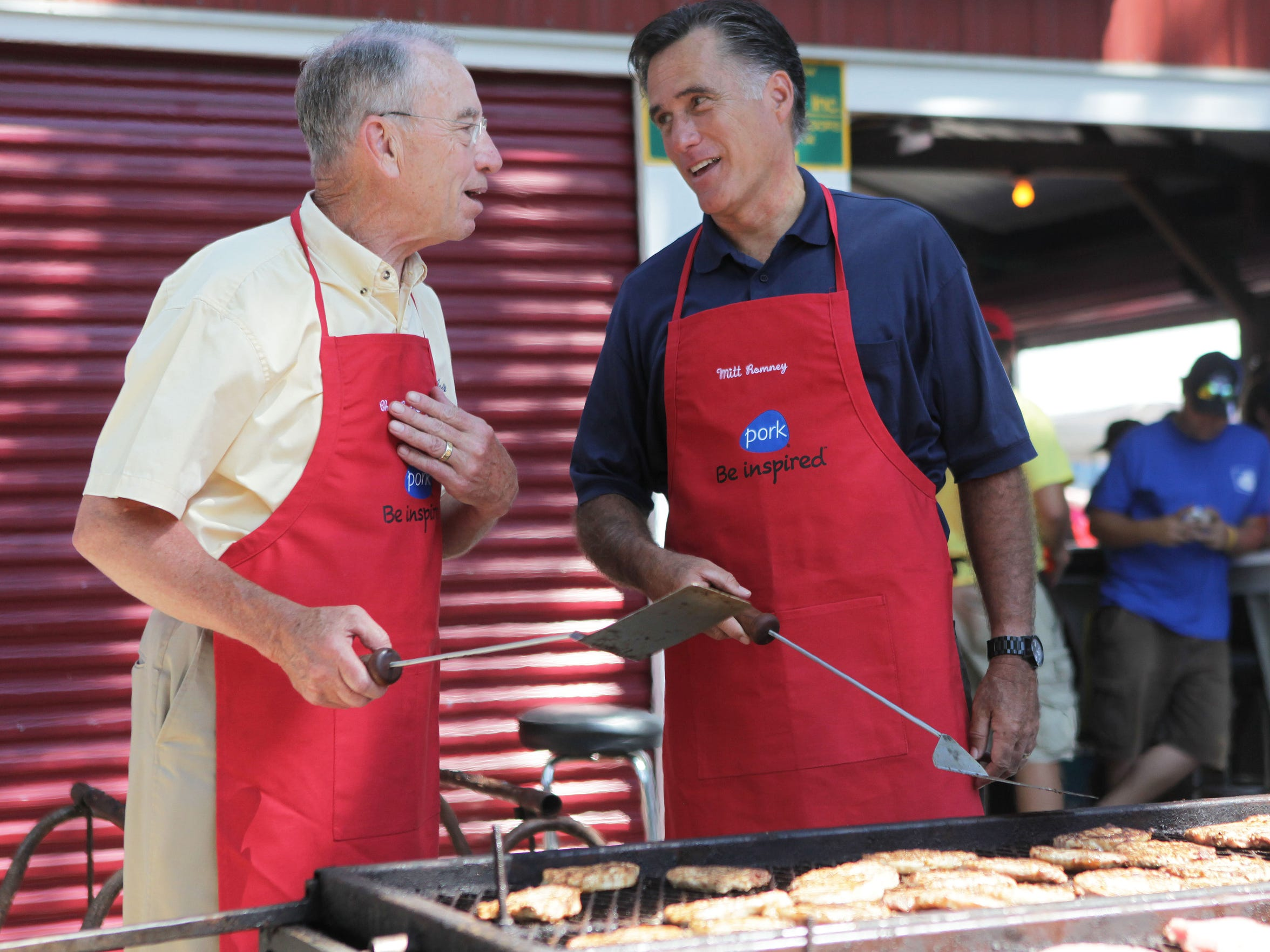 Republican presidential candidate Mitt Romney flips pork chops with Sen. Chuck Grassley at the Iowa Pork Tent at the 2011 Iowa State Fair.