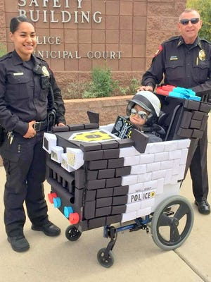 Alfadiva Peru, left, and Bayard Police Chief Willie Kerin honor Isaiah Castanon in his Lego Bad Cop costume for winning an online Halloween Costume Contest.