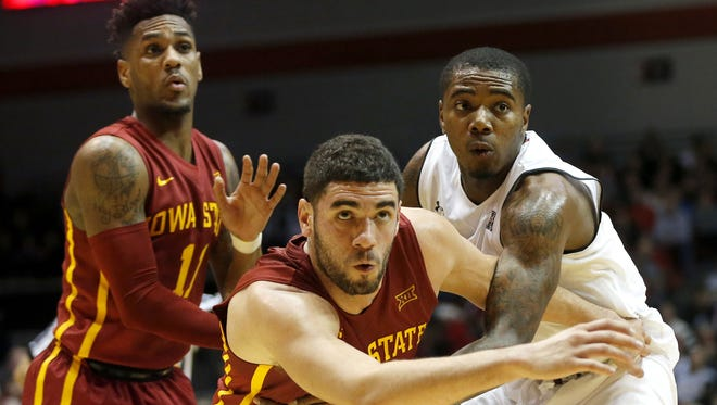 Iowa State Cyclones forward Georges Niang (31), center, and Cincinnati Bearcats forward Gary Clark (11) battle for a rebound in the first half during the NCAA basketball game between the Iowa State Cyclones and the Cincinnati Bearcats, Tuesday, Dec. 22, 2015, Fifth Third Arena in Cincinnati. Iowa State leads 45-38 at halftime.